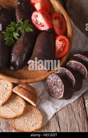 Fresh black pudding with tomato on a plate close-up. vertical top view - Stock Photo