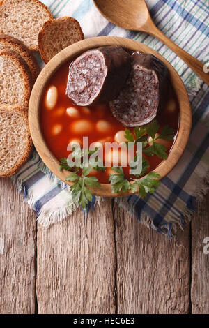 Delicious soup with black pudding Fabada asturiana in a wooden bowl. vertical top view - Stock Photo
