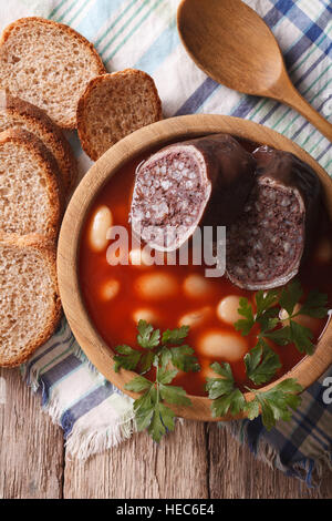Delicious soup with black pudding Fabada asturiana close up in a wooden bowl. vertical top view - Stock Photo