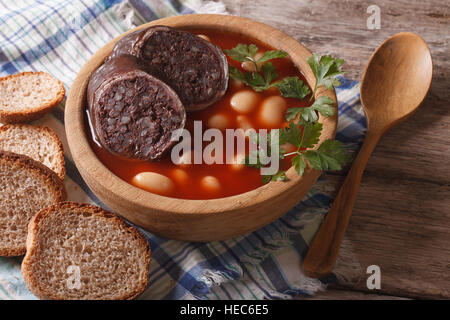 Delicious bean soup Fabada asturiana closeup in a wooden bowl. horizontal - Stock Photo
