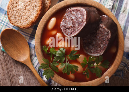 Bean soup with sausage Morcillo close up in a bowl. horizontal top view - Stock Photo
