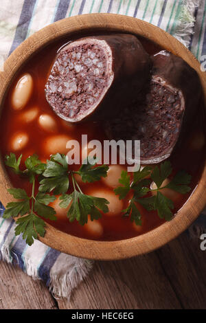 Bean soup with sausage Morcillo close up in a bowl. vertical top view - Stock Photo
