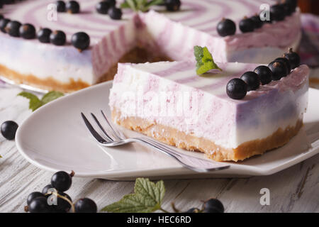 A piece of cheesecake with currant close-up on a plate. horizontal - Stock Photo
