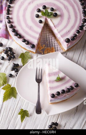 Beautiful sliced cheese cake with currants close-up on the table. vertical top view - Stock Photo