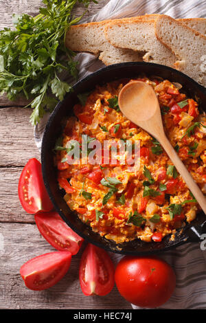Menemen in a frying pan and ingredients on the table close-up. vertical top view - Stock Photo