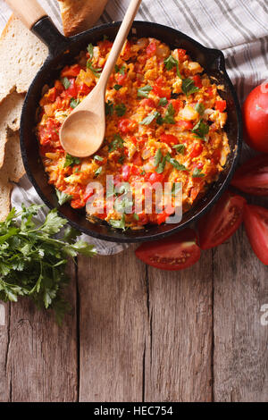Menemen in a frying pan and ingredients on the table. vertical top view - Stock Photo
