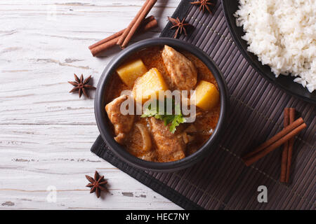 Thai massaman curry with chicken in a bowl and rice on the table. horizontal top view - Stock Photo