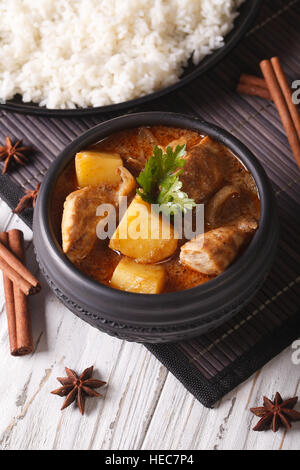 Thai Kaeng massaman curry with chicken in a bowl and rice on the table. vertical - Stock Photo