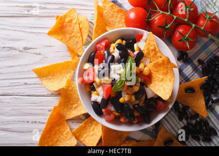 Mexican salsa with beans in a bowl and corn chips nachos on the table close-up. horizontal view from above - Stock Photo