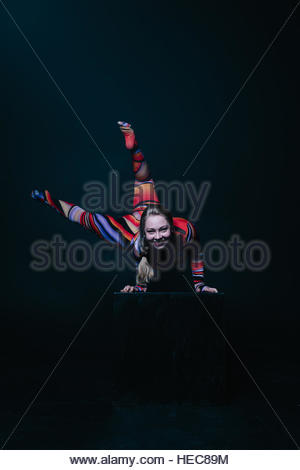 Young flexible blonde circus acrobat posing in studio in costume. Doing equilibre balance handstand on a cube. Copy - Stock Photo