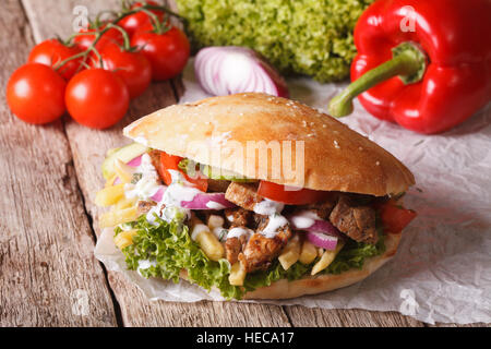 Fast Food: Doner kebab with meat, vegetables and french fries close-up on the table. horizontal - Stock Photo