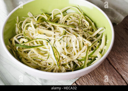 Natural food: raw zucchini pasta in a bowl close up on the table. horizontal - Stock Photo
