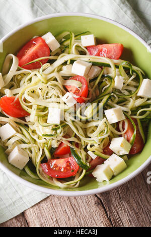 Healthy zucchini pasta with cheese and tomato close up in a bowl on the table. Vertical - Stock Photo