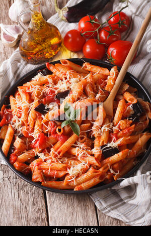 Italian food: Penne with eggplant and tomatoes close-up on the table and ingredients. Vertical - Stock Photo