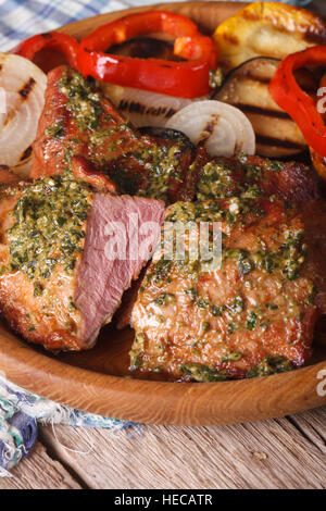 Grilled meat with pesto and vegetables close-up on a plate. vertical - Stock Photo