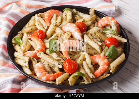 penne pasta with shrimps, tomato and pesto closeup on a plate. horizontal - Stock Photo