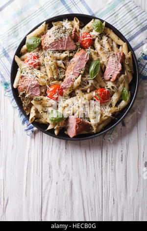 penne pasta with meat, parmesan cheese, tomatoes and pesto sauce on a plate. vertical top view - Stock Photo