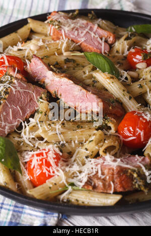 penne pasta with meat, tomato and pesto close up on a plate. vertical - Stock Photo