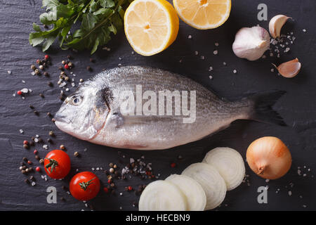 Raw fish dorado with the ingredients on the table. horizontal view from above - Stock Photo