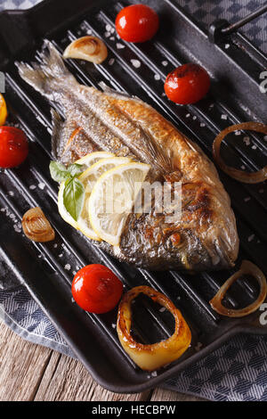 Grilled dorado fish with lemon and vegetables close-up on the grill pan. vertical - Stock Photo