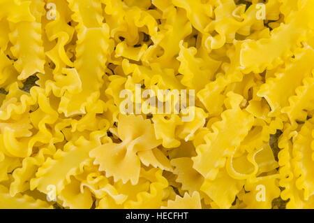 Uncooked bow tie farfalle pasta pile background - Stock Photo