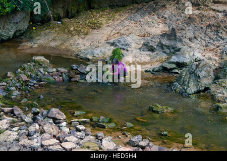 A local woman prepares a dinner salad by a rocky pool of the Lijiang River (Guilin-Yangshuo). - Stock Photo