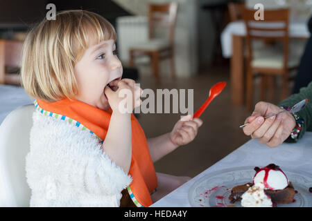two years old child with orange plastic spoon eating with hand in mouth sharing with woman a piece of chocolate - Stock Photo