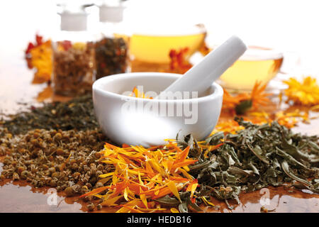 Mortar and pestle with chamomile, marigold, and vervain or verbena - Stock Photo