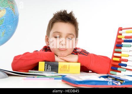 7 year-old schoolboy sitting at his desk, not concentrating - Stock Photo