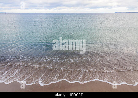 Waves and sandy beach. Coastline of the Baltic sea in wintertime. Travemuende sea resort, Germany - Stock Photo
