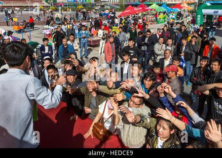 Chinese trader selling at public auction, Nanmen Square, Yinchuan, Ningxia, China - Stock Photo