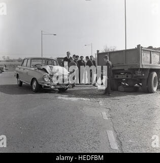 1965, historical, bystanders stand in middle of a road following a motoring accident where the front of a motor - Stock Photo