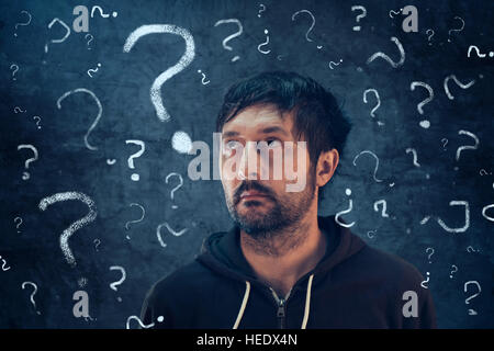 Confused man with so many questions looking for the answer to his problems - Stock Photo