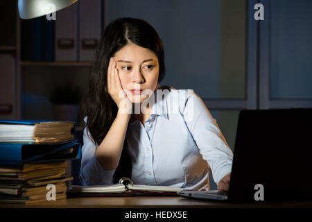 asian business woman sitting at desk sleepy working overtime late night. indoors office background - Stock Photo