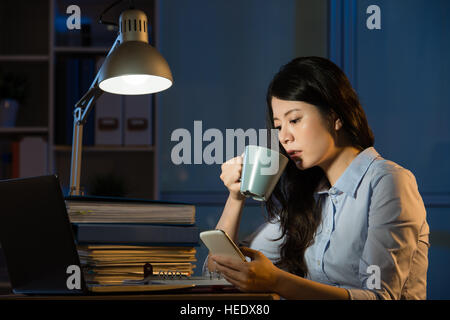 asian business woman talk on smartphone working overtime late night. indoors office background - Stock Photo