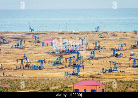 Oil pumps and rigs at the field by Caspian sea near Baku, Azerbaijan - Stock Photo