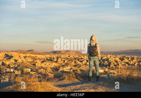 Young woman traveller in hoodie watching sunrise, Cappadocia, Central Turkey - Stock Photo