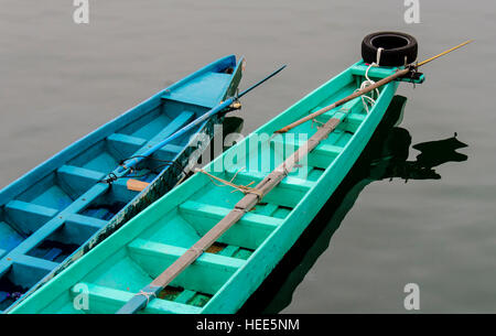 Two row boats floating side by side in water - Stock Photo