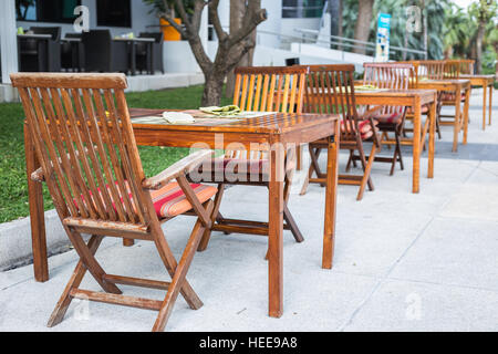 Row of wooden table with chair in the garden - Stock Photo
