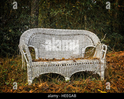 Old white wicker chair out in a wooded area along side a road by an old burnt out house home - Stock Photo