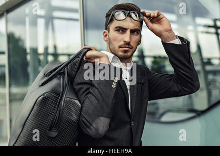 Close-up face of confident handsome elegant businessman staring at the camera in glasses. Outdoor airport background, - Stock Photo