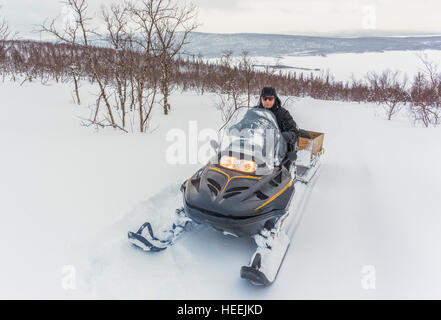 Man driving a snowmobile up on a mountain with birch trees around and a frozen lake in the background, Gällivare, - Stock Photo