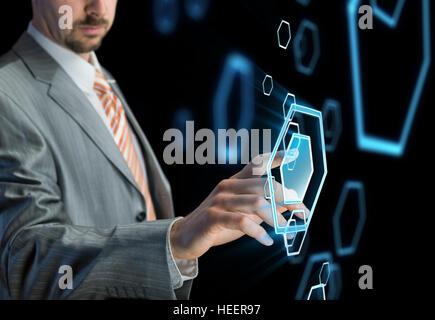 Businessman touching button on futuristic virtual screen, black background - Stock Photo