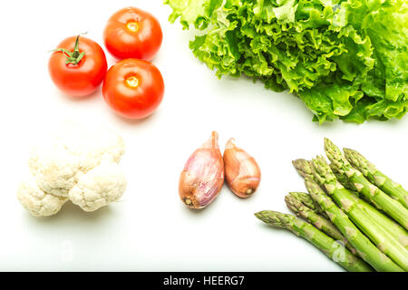 Tomatoes, cauliflower, shallots, asparagus and a green salad on a white background. - Stock Photo