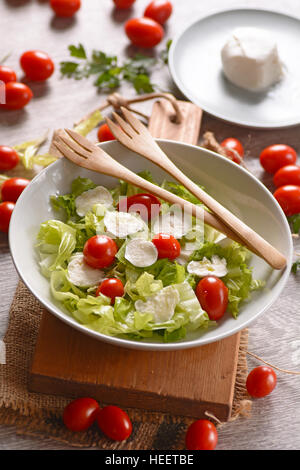 lettuce salad, mozzarella and tomato - Traditional Italian recipe - Stock Photo