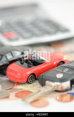 Buying or renting a car concept with car toys, car key, coins and bills - Stock Photo