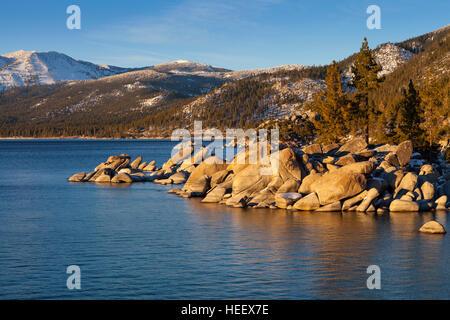 Sand Harbor, Lake Tahoe, Nevada at Sunset with rocks and trees on shoreline. - Stock Photo