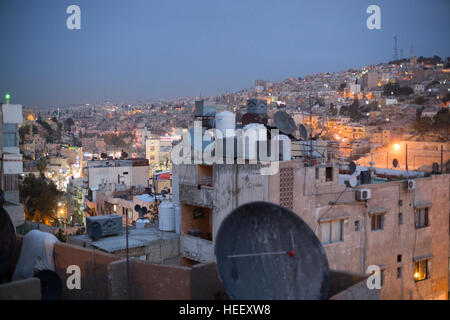 Satellite dishes and water storage tanks sit on a rooftop in Amman, Jordan near the ancient Roman amphitheatre. - Stock Photo