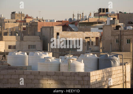 Water storage tanks sit on a rooftop in Zarqa, Jordan. - Stock Photo