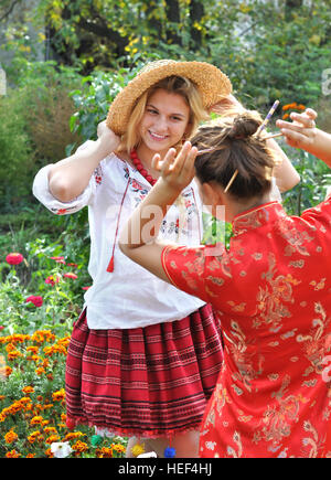two teenage girls in traditional ukrainian and chinese  clothes in  the summer landscape - Stock Photo